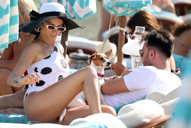 Στην παραλία με τεράστιο καπέλο και το σκυλάκι της στην αγκαλιά